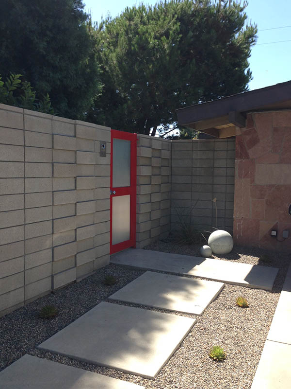Modern concrete and stone courtyard with red gate